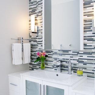 Immagine di una stanza da bagno contemporanea di medie dimensioni con ante lisce, ante bianche, piastrelle multicolore, piastrelle a listelli, pareti grigie, WC a due pezzi e lavabo integrato