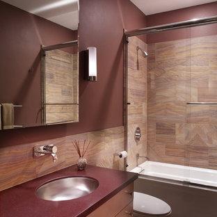 Modelo de cuarto de baño minimalista con lavabo bajoencimera, armarios con paneles lisos y combinación de ducha y bañera
