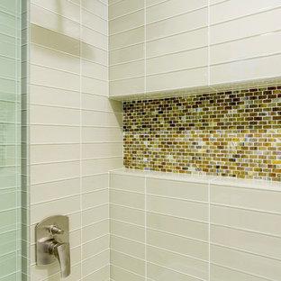 Immagine di una stanza da bagno padronale design di medie dimensioni con ante lisce, ante in legno scuro, vasca da incasso, piastrelle beige, piastrelle di vetro, pavimento in pietra calcarea, lavabo a bacinella, top in quarzo composito, pavimento beige, pareti beige e porta doccia scorrevole