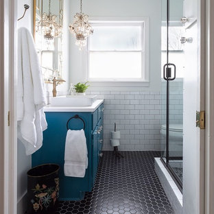 Imagen de cuarto de baño con ducha, tradicional, con armarios con paneles lisos, puertas de armario azules, ducha esquinera, baldosas y/o azulejos blancos, baldosas y/o azulejos de cemento, paredes blancas, lavabo sobreencimera, suelo negro y ducha con puerta con bisagras