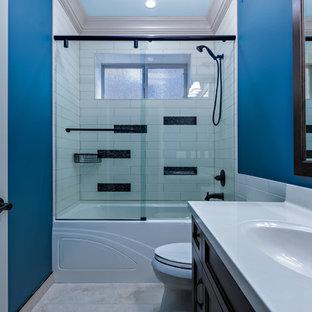 Esempio di una stanza da bagno chic di medie dimensioni con lavabo integrato, ante con riquadro incassato, ante in legno bruno, top in quarzo composito, vasca ad alcova, vasca/doccia, WC monopezzo, piastrelle beige, piastrelle in ceramica, pareti blu e pavimento in travertino