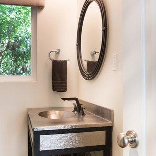 Idee per una stanza da bagno con doccia tradizionale di medie dimensioni con lavabo integrato, consolle stile comò, ante nere, top in acciaio inossidabile, doccia ad angolo, WC a due pezzi, piastrelle grigie, piastrelle in gres porcellanato, pareti beige e pavimento in gres porcellanato