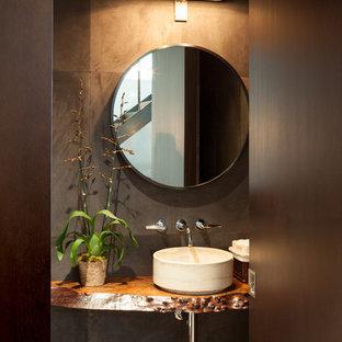 Foto de cuarto de baño con ducha, moderno, pequeño, con lavabo sobreencimera, armarios tipo mueble, puertas de armario negras, baldosas y/o azulejos de cemento, paredes grises, suelo de madera clara y encimera de cobre