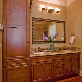 サンフランシスコの中サイズのトラディショナルスタイルのおしゃれな浴室 (アンダーカウンター洗面器、シェーカースタイル扉のキャビネット、中間色木目調キャビネット、御影石の洗面台、アルコーブ型浴槽、シャワー付き浴槽、一体型トイレ、ベージュのタイル、磁器タイル、ベージュの壁、無垢フローリング、茶色い床、シャワーカーテン、ベージュのカウンター) の写真