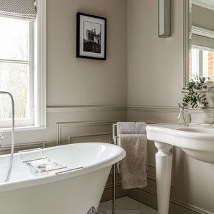 На фото: детская ванная комната среднего размера в стиле неоклассика (современная классика) с белыми фасадами, ванной на ножках, серыми стенами, мраморным полом, белым полом, белой столешницей, тумбой под одну раковину, напольной тумбой и панелями на части стены с