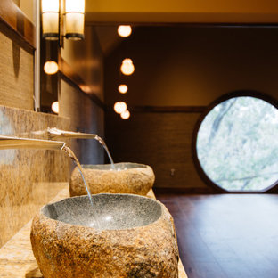 This is an example of a modern master bathroom in Nashville with furniture-like cabinets, medium wood cabinets, a japanese tub, a shower/bathtub combo, a wall-mount toilet, gray tile, pebble tile, grey walls, a vessel sink, marble benchtops, a hinged shower door, yellow benchtops, a niche, a double vanity, a built-in vanity, decorative wall panelling, medium hardwood floors and brown floor.