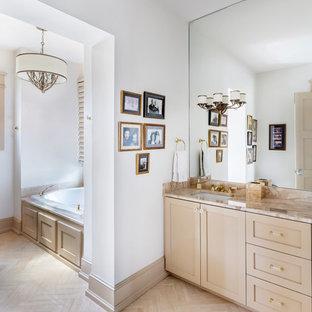 Diseño de cuarto de baño principal, tradicional, de tamaño medio, con armarios con paneles empotrados, puertas de armario beige, bañera encastrada, sanitario de dos piezas, paredes blancas, suelo de madera clara, lavabo bajoencimera, encimera de piedra caliza, suelo beige y encimeras beige