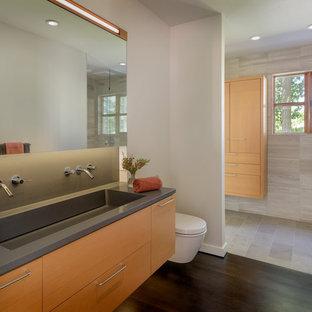 Immagine di una stanza da bagno padronale minimalista di medie dimensioni con ante lisce, ante in legno scuro, WC sospeso, pareti bianche, parquet scuro, lavabo integrato, top in quarzo composito, pavimento nero, piastrelle grigie, top grigio e piastrelle in travertino