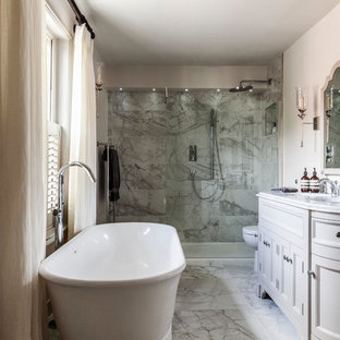 Photo of a medium sized country ensuite bathroom in Surrey with grey cabinets, a freestanding bath, a one-piece toilet, grey tiles, marble tiles, marble flooring, a submerged sink, marble worktops, grey floors, white worktops, recessed-panel cabinets, a built-in shower, beige walls and a hinged door.