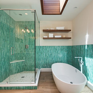 Design ideas for a tropical master bathroom in Miami with a freestanding tub, a corner shower, blue tile, green tile, matchstick tile, beige walls, brown floor and a hinged shower door.