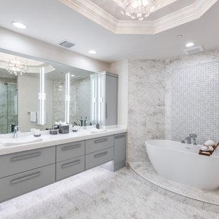 Modelo de cuarto de baño contemporáneo con armarios con paneles lisos, puertas de armario grises, bañera exenta, baldosas y/o azulejos grises, lavabo encastrado, suelo gris y encimeras blancas