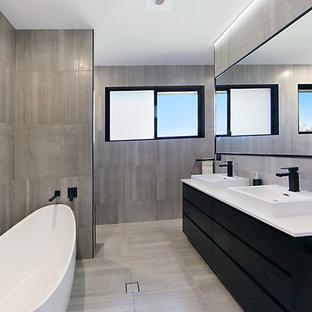 Ejemplo de cuarto de baño principal, contemporáneo, de tamaño medio, con armarios con paneles lisos, puertas de armario negras, bañera exenta, baldosas y/o azulejos marrones, paredes marrones, lavabo sobreencimera, encimera de granito, suelo marrón, encimeras blancas, ducha empotrada y ducha abierta