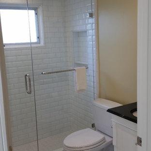 Ispirazione per una piccola stanza da bagno con doccia design con lavabo sottopiano, ante in stile shaker, ante bianche, top in granito, WC a due pezzi, piastrelle nere, piastrelle in gres porcellanato, pareti bianche e pavimento in gres porcellanato
