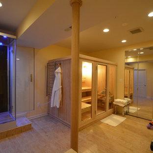 Modelo de sauna moderna, grande, con armarios tipo vitrina, ducha esquinera, baldosas y/o azulejos negros, paredes amarillas y suelo de madera clara