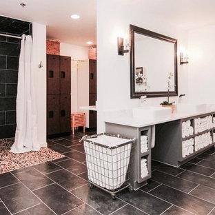 Foto de cuarto de baño actual, de tamaño medio, con armarios abiertos, puertas de armario grises, ducha abierta, baldosas y/o azulejos de pizarra, paredes grises, suelo de pizarra, lavabo sobreencimera, encimera de acrílico, suelo gris y encimeras blancas