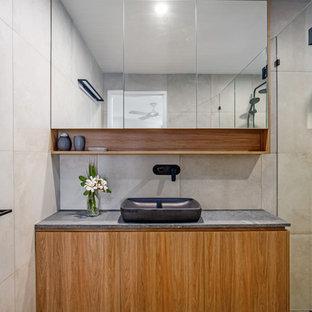 Ejemplo de cuarto de baño infantil, costero, de tamaño medio, con armarios tipo mueble, puertas de armario de madera oscura, ducha doble, baldosas y/o azulejos grises, baldosas y/o azulejos de porcelana, paredes grises, suelo de baldosas de porcelana, lavabo sobreencimera, encimera de cemento, suelo gris, ducha con puerta con bisagras y encimeras grises