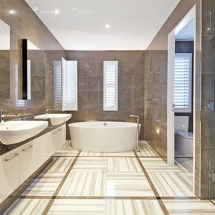 Photo of a contemporary master bathroom in Brisbane with flat-panel cabinets, white cabinets, a freestanding tub, an alcove shower, a two-piece toilet, gray tile, grey walls, an integrated sink, grey floor, a hinged shower door and black benchtops.