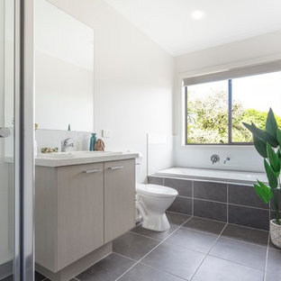 Design ideas for a contemporary bathroom in Melbourne with flat-panel cabinets, light wood cabinets, a drop-in tub, white tile, white walls, a drop-in sink, grey floor and white benchtops.