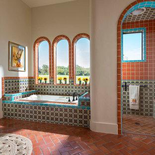 Cette photo montre une salle de bain principale sud-ouest américain avec un carrelage multicolore, des carreaux en terre cuite, un sol en carreau de terre cuite, une baignoire posée, une douche d'angle, un mur beige et une cabine de douche à porte battante.