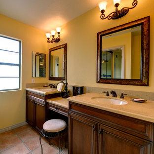 Medelhavsstil inredning av ett beige beige en-suite badrum, med luckor med infälld panel, skåp i mellenmörkt trä, en dusch i en alkov, gul kakel, gula väggar, klinkergolv i terrakotta, ett undermonterad handfat, bänkskiva i kvarts, rosa golv och dusch med gångjärnsdörr