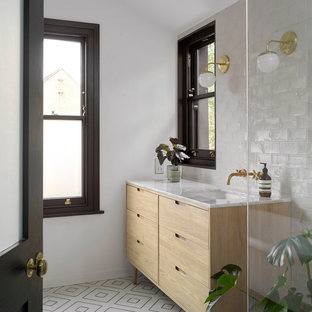 Photo of a contemporary bathroom in London with flat-panel cabinets, light wood cabinets, white tiles, white walls, a submerged sink, multi-coloured floors and white worktops.