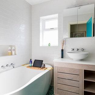 Foto på ett litet funkis badrum med dusch, med släta luckor, skåp i ljust trä, ett fristående badkar, en vägghängd toalettstol, beige kakel, porslinskakel, beige väggar, klinkergolv i porslin, ett fristående handfat, bänkskiva i akrylsten, grönt golv och med dusch som är öppen
