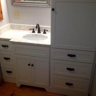 ブリッジポートの中サイズのトラディショナルスタイルのおしゃれなバスルーム (浴槽なし) (シェーカースタイル扉のキャビネット、白いキャビネット、分離型トイレ、グレーの壁、無垢フローリング、アンダーカウンター洗面器、珪岩の洗面台、茶色い床) の写真