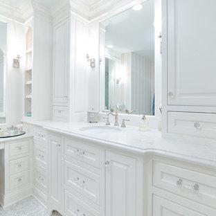 Klassisk inredning av ett mellanstort vit vitt en-suite badrum, med luckor med infälld panel, vita skåp, vita väggar, klinkergolv i keramik, ett undermonterad handfat och marmorbänkskiva