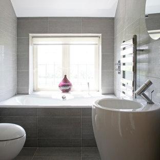 Mittelgroßes Modernes Badezimmer mit Einbaubadewanne, Wandtoilette, grauen Fliesen, Porzellanfliesen, grauer Wandfarbe, Porzellan-Bodenfliesen und Sockelwaschbecken in London