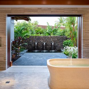 Réalisation d'une salle de bain principale ethnique avec une baignoire indépendante, une douche ouverte, un carrelage gris, un carrelage de pierre, un mur beige et aucune cabine.