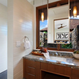 Mid-sized island style white tile and porcelain tile gray floor bathroom photo in Hawaii with flat-panel cabinets, medium tone wood cabinets, white walls, an undermount sink, granite countertops and multicolored countertops