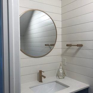 Foto di una piccola stanza da bagno con doccia country con ante in stile shaker, ante blu, WC a due pezzi, pareti bianche, pavimento in laminato, lavabo sottopiano, top in quarzo composito, pavimento marrone e top bianco