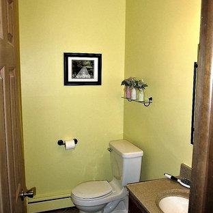 Foto di una piccola stanza da bagno chic con WC a due pezzi, pareti gialle, pavimento in linoleum, lavabo sottopiano, top in laminato e pavimento marrone