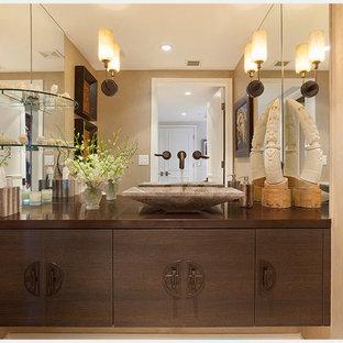 Diseño de cuarto de baño actual, de tamaño medio, con armarios con paneles lisos, puertas de armario de madera en tonos medios, paredes beige, lavabo sobreencimera, encimera de cobre y encimeras marrones