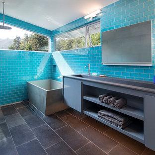 Foto på ett mellanstort funkis grå en-suite badrum, med släta luckor, grå skåp, ett fristående badkar, blå kakel, glaskakel, skiffergolv, ett avlångt handfat, bänkskiva i akrylsten, svart golv, med dusch som är öppen och våtrum
