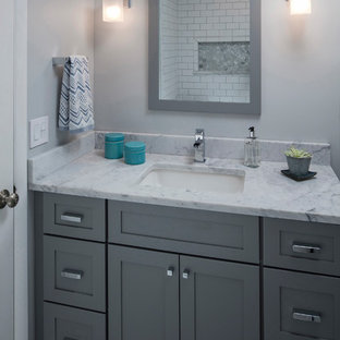 This is an example of a mid-sized traditional kids bathroom in Philadelphia with shaker cabinets, grey cabinets, an alcove tub, an alcove shower, a one-piece toilet, white tile, porcelain tile, grey walls, marble floors, an undermount sink, marble benchtops, multi-coloured floor and a hinged shower door.