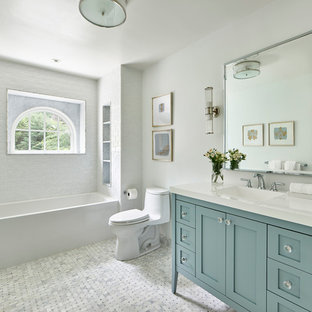 Inspiration for a large transitional master white tile and porcelain tile marble floor and white floor bathroom remodel in Philadelphia with shaker cabinets, turquoise cabinets, a one-piece toilet, white walls, an integrated sink, solid surface countertops and white countertops