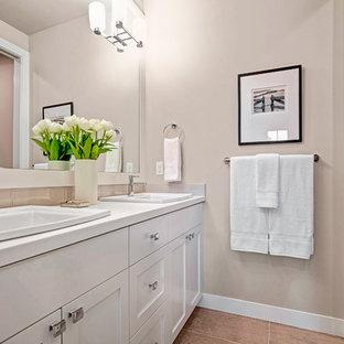Modelo de cuarto de baño de estilo americano con puertas de armario blancas, bañera encastrada, sanitario de una pieza, baldosas y/o azulejos de cerámica, paredes grises, suelo de baldosas de porcelana, lavabo bajoencimera, ducha con cortina, encimeras blancas, encimera de acrílico y combinación de ducha y bañera