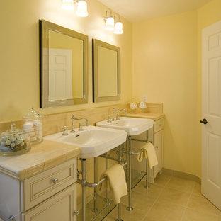 Foto di una stanza da bagno per bambini tradizionale di medie dimensioni con ante con riquadro incassato, ante rosse, vasca/doccia, WC a due pezzi, piastrelle in ceramica, pareti gialle, pavimento con piastrelle in ceramica, lavabo a colonna, top piastrellato e piastrelle beige
