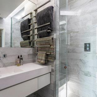 Kleines Modernes Badezimmer En Suite mit Glasfronten, grauen Fliesen, Keramikfliesen, Keramikboden, Mineralwerkstoff-Waschtisch, grauem Boden, Falttür-Duschabtrennung, weißer Waschtischplatte, bodengleicher Dusche, grauer Wandfarbe und integriertem Waschbecken in Surrey