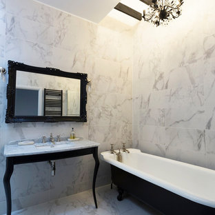Photo of a medium sized bohemian ensuite bathroom in Surrey with a freestanding bath, marble tiles, ceramic flooring, marble worktops, white floors, white walls, grey worktops, white tiles and a submerged sink.