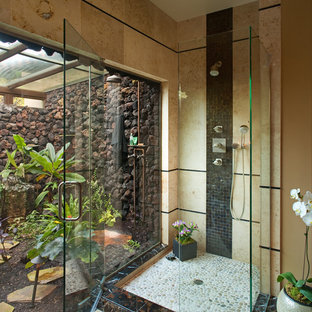 Inspiration for a mid-sized tropical master black tile and stone tile ceramic floor doorless shower remodel in San Diego with a one-piece toilet, beige walls, a vessel sink and a hinged shower door