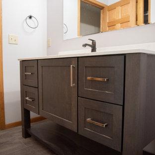 Imagen de cuarto de baño moderno, de tamaño medio, con armarios con paneles lisos, puertas de armario de madera en tonos medios, combinación de ducha y bañera, paredes grises, lavabo integrado, encimera de acrílico, suelo gris, ducha con cortina y encimeras blancas
