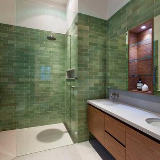 Diseño de cuarto de baño actual con lavabo bajoencimera, armarios con paneles lisos, puertas de armario de madera oscura, ducha a ras de suelo, baldosas y/o azulejos verdes y baldosas y/o azulejos de cemento