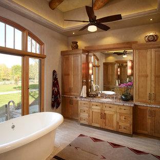 Idées déco pour une salle de bain principale sud-ouest américain avec un placard avec porte à panneau encastré, des portes de placard en bois clair, un plan de toilette en granite, une baignoire indépendante, un mur beige et un sol en carrelage de céramique.