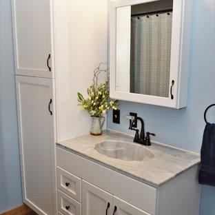 Idee per una piccola stanza da bagno con doccia country con ante in stile shaker, ante bianche, doccia alcova, lavabo integrato, top in marmo, pavimento marrone, porta doccia scorrevole, top blu e pareti blu