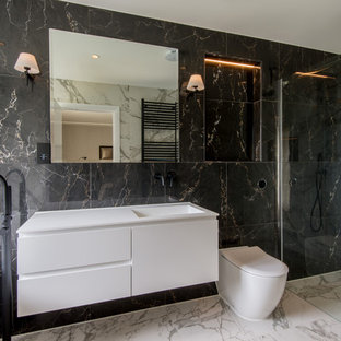 Inspiration for a contemporary bathroom in London with flat-panel cabinets, white cabinets, a freestanding bath, a built-in shower, a one-piece toilet, an integrated sink, white floors, a hinged door and white worktops.