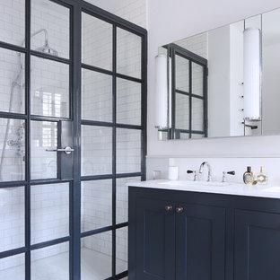 Modelo de cuarto de baño con ducha, nórdico, de tamaño medio, con armarios estilo shaker, puertas de armario azules, paredes blancas, lavabo bajoencimera, suelo de linóleo, ducha abierta, baldosas y/o azulejos blancos, baldosas y/o azulejos de cemento y ducha con puerta con bisagras