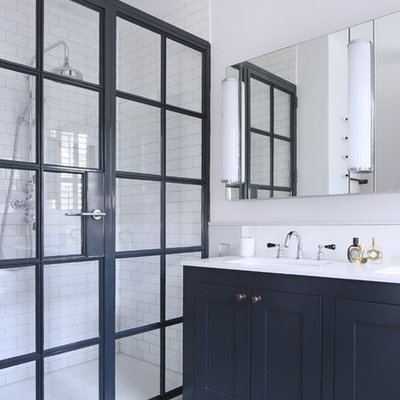 Doorless shower - mid-sized scandinavian 3/4 white tile and subway tile linoleum floor doorless shower idea in London with shaker cabinets, blue cabinets, white walls, an undermount sink and a hinged shower door