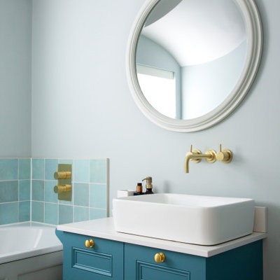 Example of a small transitional 3/4 blue tile, green tile and ceramic tile drop-in bathtub design in London with recessed-panel cabinets, blue cabinets, blue walls, a vessel sink and white countertops